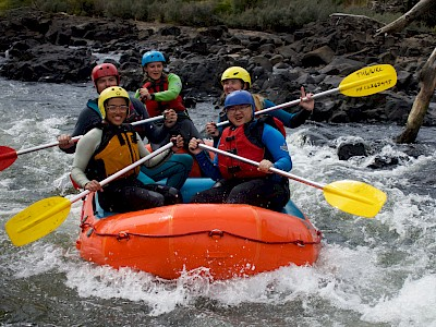 5 rafters heading through some mild rapids