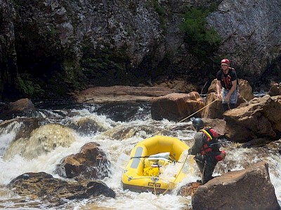 Two people guiding a raft through some rapids with ropes